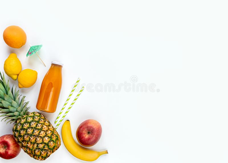 Top view of various fruits, a bottle of freshly squeezed multivitamin juice and cocktail accessories on a white background. Copy stock image