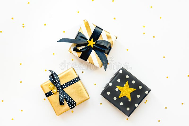 Top view of various gift boxes over star shaped golden sequins white background stock photography