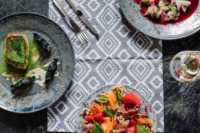 top view of various gourmet dishes and glass of wine on marble stock photo