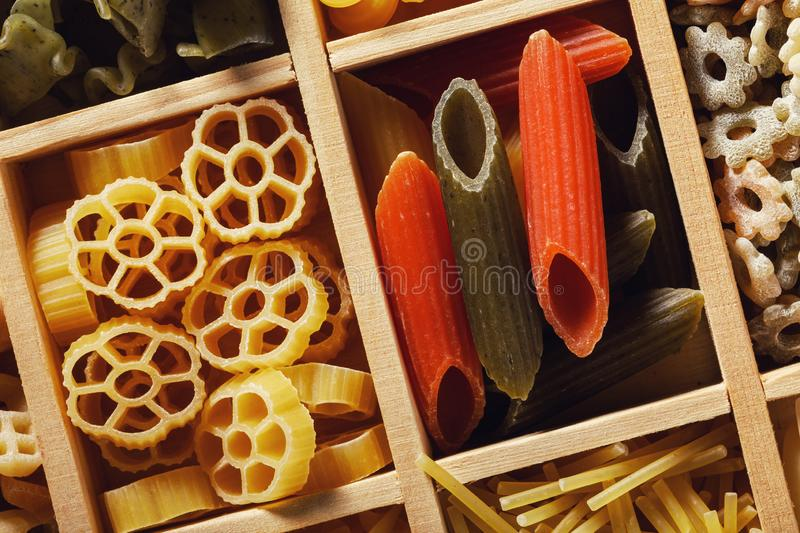 Top view on various pasta in a wooden box royalty free stock photo