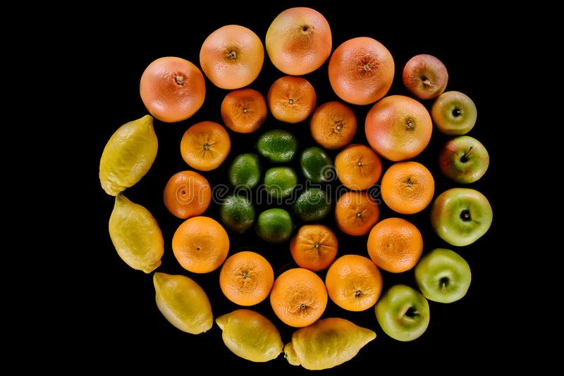 Top view of various ripe citrus fruits composition in spiral shape. Isolated on black stock images