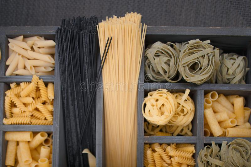 Top view Various types of Italian pasta in a wooden box with different cells. stock photo