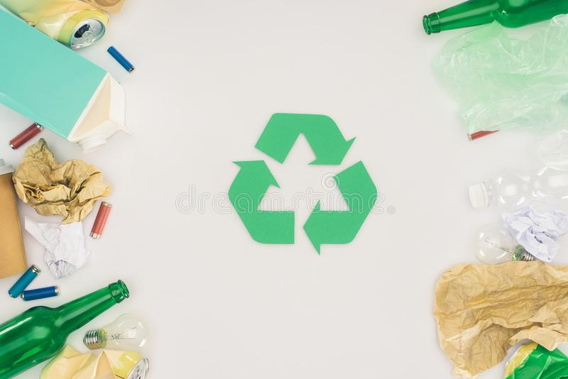 top view of various types of trash surrounding recycle sign royalty free stock images
