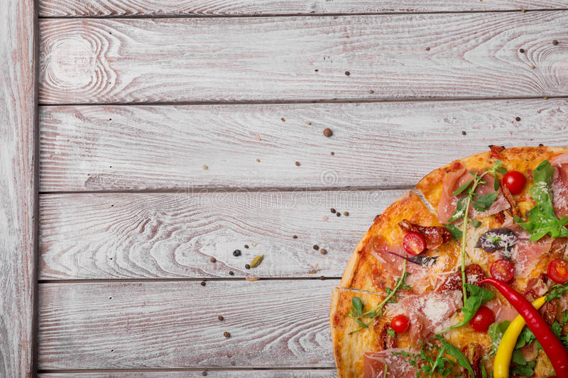 Top view of vegetable pizza on a wooden background, close-up. A half of pancetta pizza with vegetables and spicy stock photo
