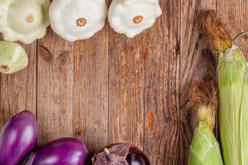 Top view of vegetables on wood with copy space. Organic vegetarian food. Top view of vegetables on wood with copy space. Healthy food - corn, eggplants and royalty free stock images