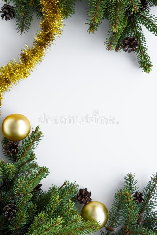 Top view on vertical composition of ornaments such as gold baubles, tinsel, evergreen tree branches and cones. Christmas greeting. Top view on vertical stock photo