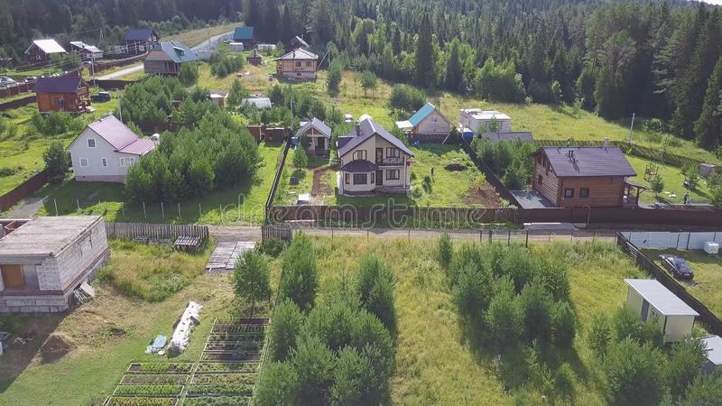 Top view of village in forest. Clip. From village cottage comes man for walk. Village life with modern cottages in. Forest stock image