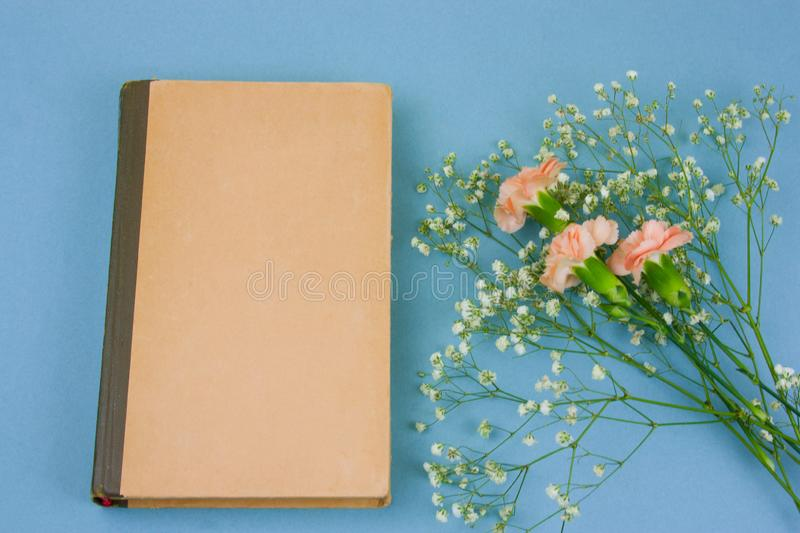 Vintage book with empty sheets and flowers on a pastel blue background. Top view vintage book with empty sheets and flowers on a pastel blue background royalty free stock photo
