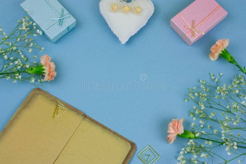 Vintage book with empty sheets , gift boxes and flowers on a pastel blue background. Top view vintage book with empty sheets , gift boxes and flowers on a pastel stock photo