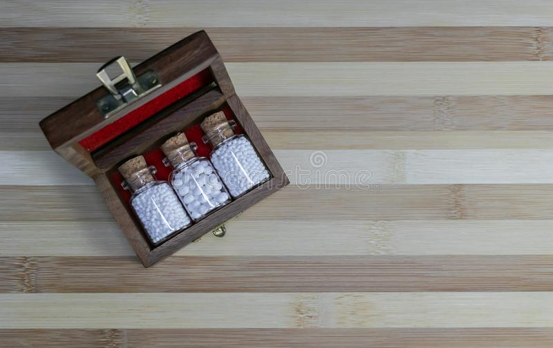 Top view of vintage Bottles of homeopathic pills in a retro styled opened wooden box on wood background stock photo