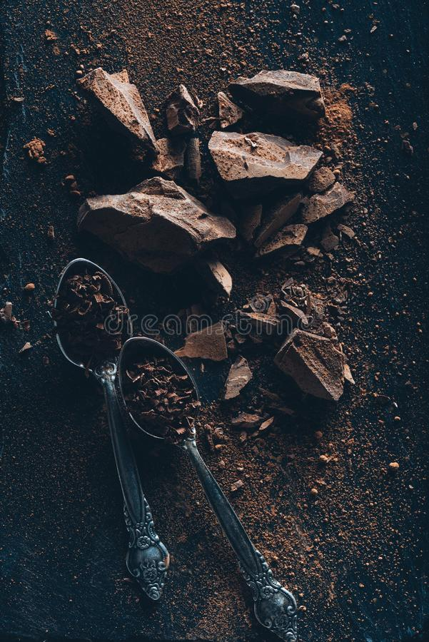 Top view of vintage spoons, chocolate pieces and cocoa powder. On dark surface royalty free stock photography