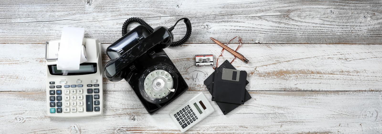 Top view of Vintage technologies that includes rotary dial phone and old computer data storage devices plus calculators. Overhead view of Vintage technologies royalty free stock images