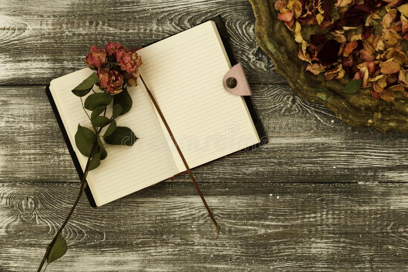Top view of vintage tray with petals of dried rose flowers and a diary or notebook and dried rose flower on a gray wooden table. F stock image