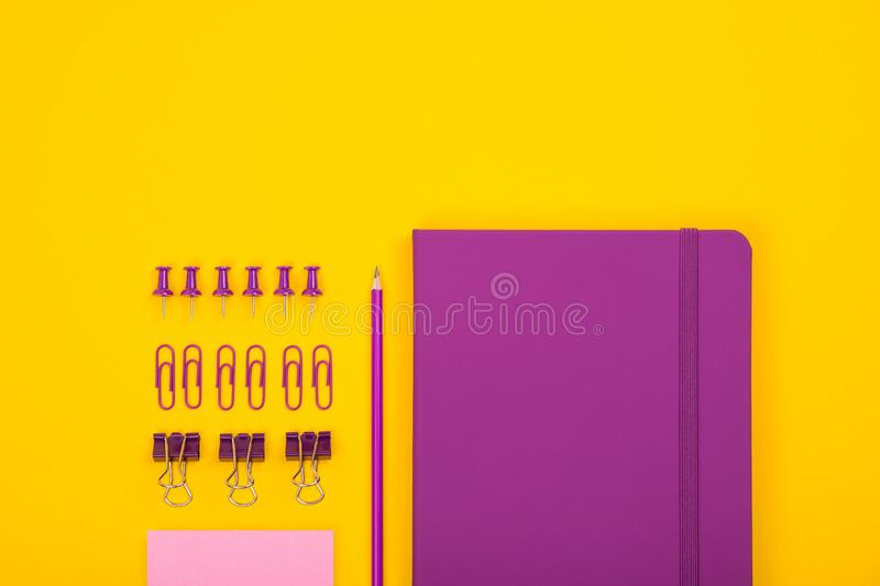 Top view of violet notebook, pencil, clips and others stationary. School accessories or office supplies. Top view of violet notebook, pencil, clips and others stock images