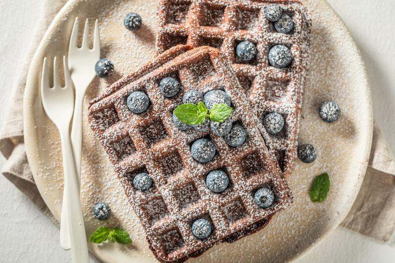 Waffles with dark chocolate on white table royalty free stock photo