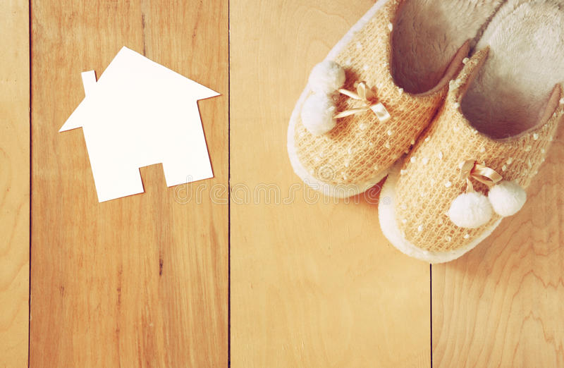 Top view of warm woman slippers over wooden floor and paper house shape as welcome home concept stock photos