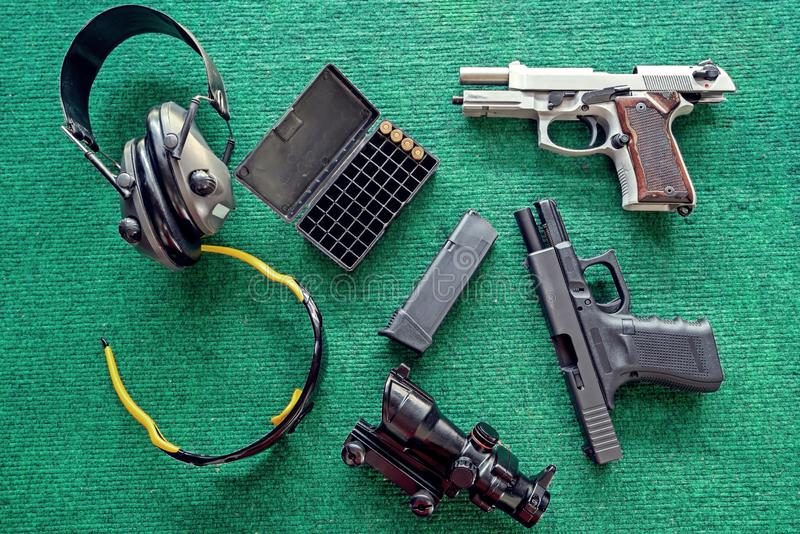 Top view weapons : Two pistols, Ear Muffs and bullets and Semi-automatic gun for self-defense on green table royalty free stock image