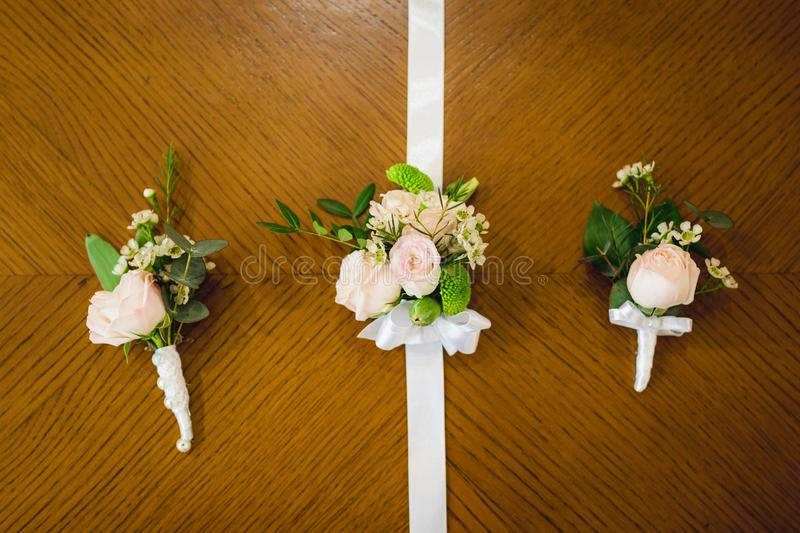 Top view of wedding boutonniere for the groom and bridesmaids on wooden background, free space. copy space. stock images