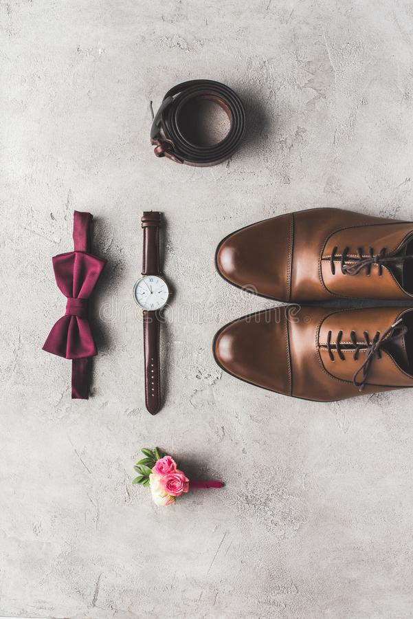Top view of wedding bow tie, boutonniere, wristwatch and shoes for groom. On gray surface royalty free stock image