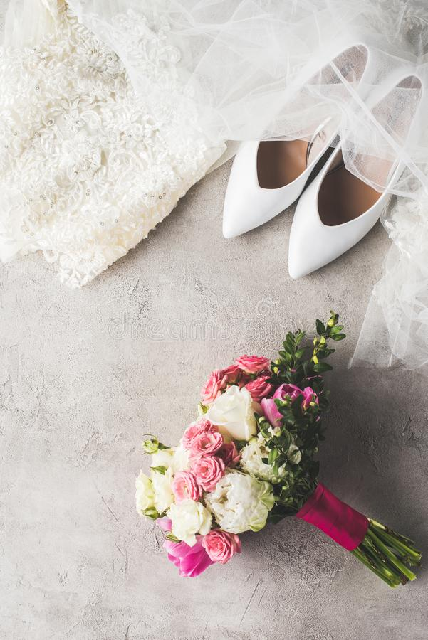Top view of wedding dress, shoes and bouquet. On gray surface stock photography