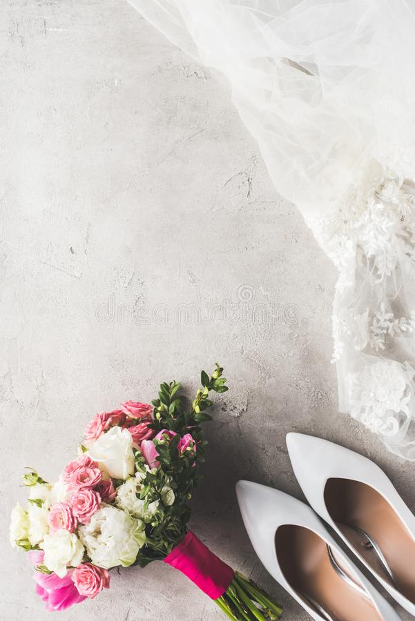 Top view of wedding dress, shoes and bouquet. On gray surface royalty free stock photos