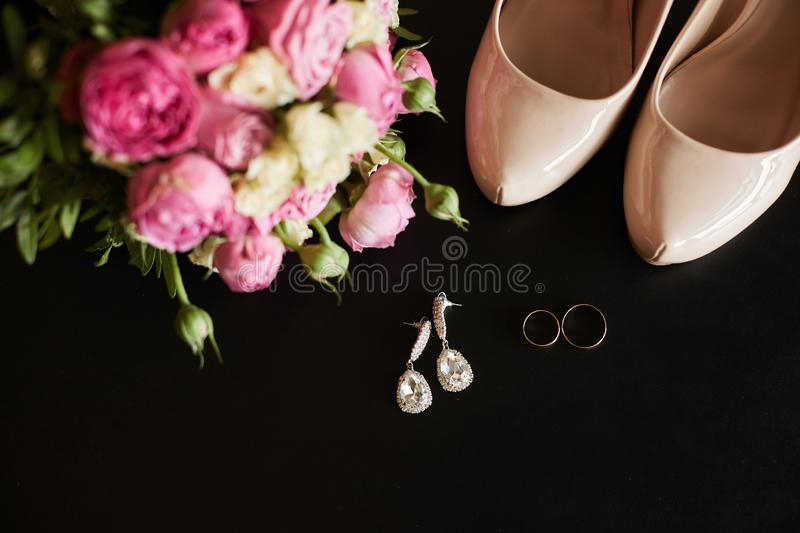 Top view of wedding rings, earrings, beautiful bouquet of pink flowers and female shoes  at black background royalty free stock photos
