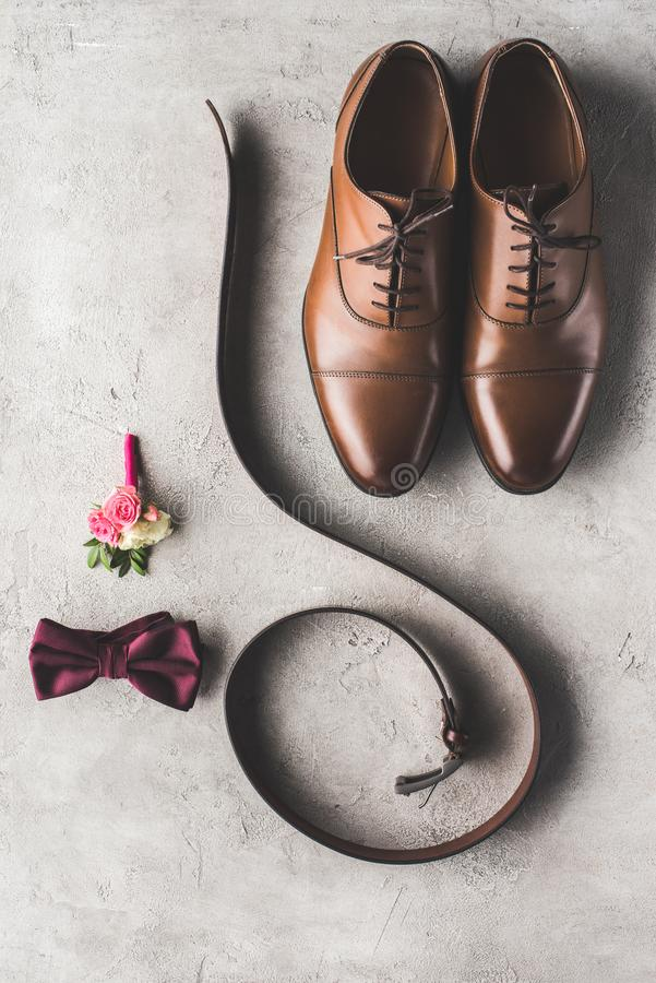 Top view of wedding shoes, bow tie, boutonniere and belt. On gray surface royalty free stock photo