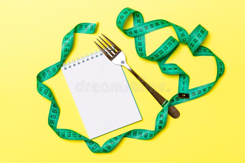 Top view of weight loss concept on yellow background. Mix of green centimeter tape, note pad and fork with space for your design.  royalty free stock images