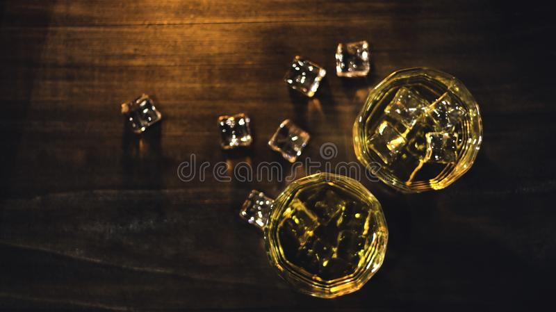 Top view whiskey in glass with beautiful amber ice, placed on a wooden table with a rough surface against a dark background and royalty free stock photography