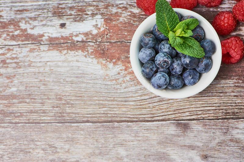 Top view on a white bowl with blueberries beside some raspberries on wooden surface royalty free stock images