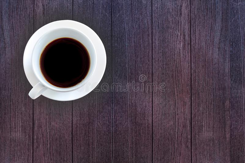 Top view White ceramic cup of black coffee on dark wooden background. Freshness in morning concept. Copy space for your text stock photo