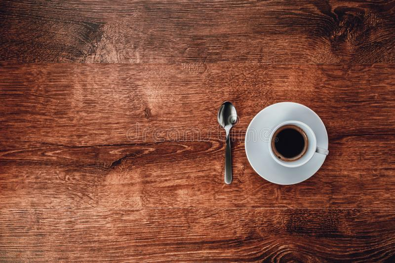 Top view of white Cup with black coffee on a white saucer and teaspoon on dark brown wooden background royalty free stock images