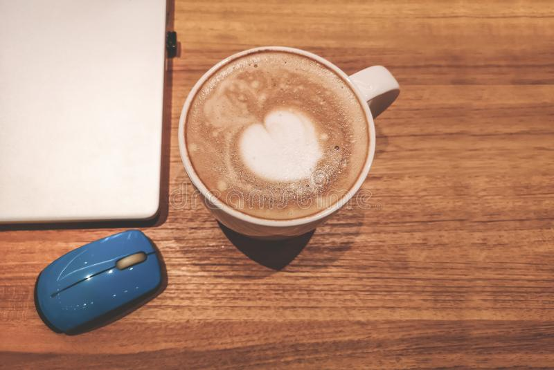 Top view, a white cup hot capuccino with white heart mug on top, a computer labtop and blue mouse on brown wooden table. Top view, a white cup hot capuccino with stock photo