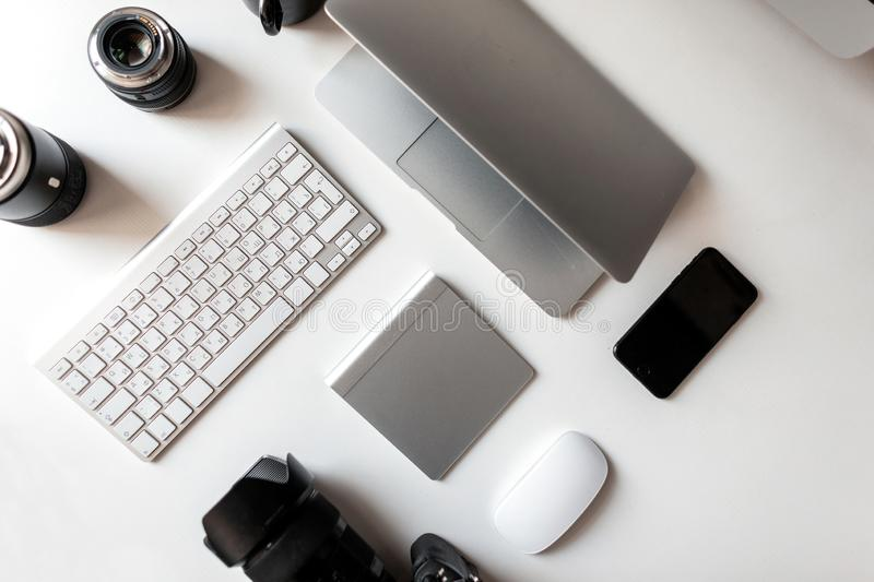 Top view of the white desktop on which lies the professional lenses to the camera, laptop, keyboard, telephone, wireless mouse stock photography