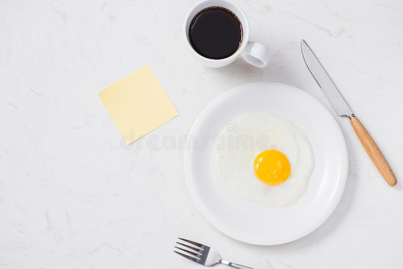 Top view of white dish with fried egg on white background.  royalty free stock photography