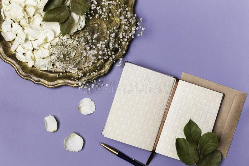 Top view of white dry petals of a flower of roses and an envelope out of Kraft paper on a blue background. Flat lay, space for royalty free stock photography