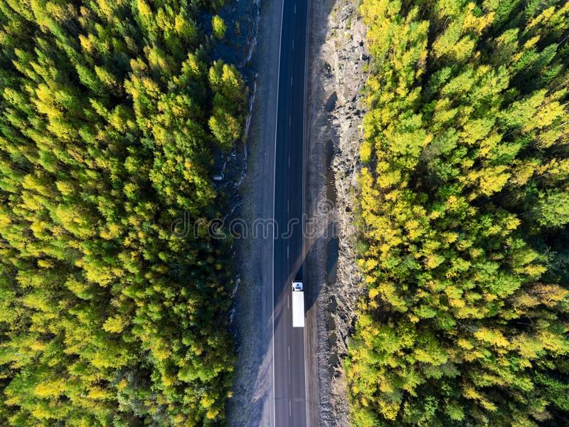 Top view at white freight truck driving between rock tunnel in golden autumn forest of Karelia, Russia royalty free stock photos