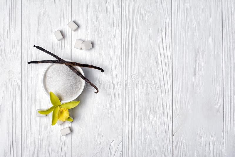 Top view of white granulated and cubes sugar with vanilla sticks and flower. On light wooden background with copy space stock photos