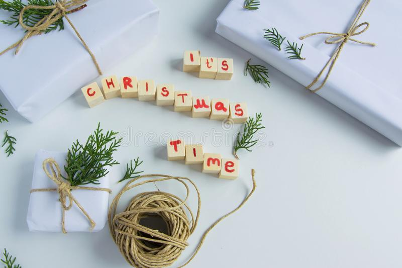 Top view of white handcraft gift boxes with `It`s Chrismas time` text wooden letters and fresh fir branches on white background royalty free stock photos
