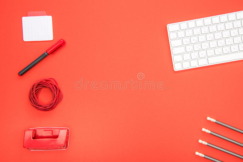 Top view of white keyboard and organized office supplies. On red background stock photos