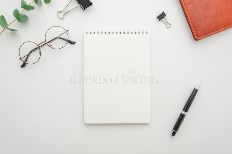 Top view of white office desktop with blank spiral notepad, glasses, supplies and leather wallet. Mock up stock photography