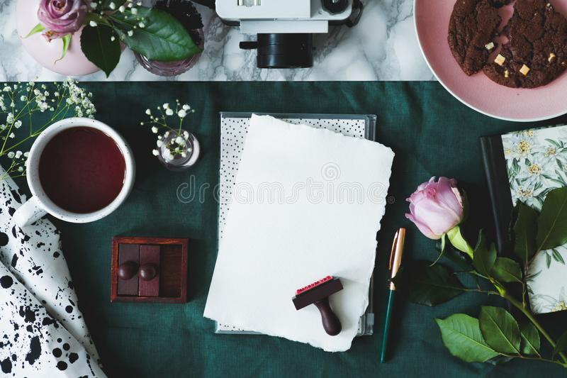Top view of white paper sheets, coffee, rose, stamps, cake, camera on a green background royalty free stock photo