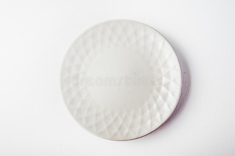 Top view of a white pastel plate on a pastel white background. Minimalism food photography. Geometric style. Copy space stock image