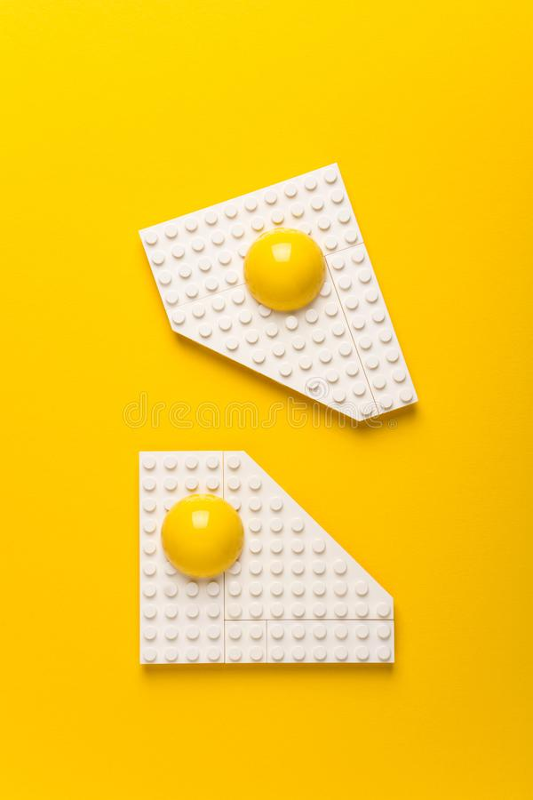 Top view of white plate with fried eggs of children`s designer on yellow paper background. Good morning concept. Top view. Flat lay royalty free stock photo