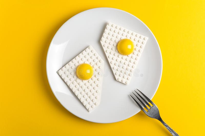 Top view of white plate with fried eggs of children`s designer on yellow paper background. Good morning concept royalty free stock images