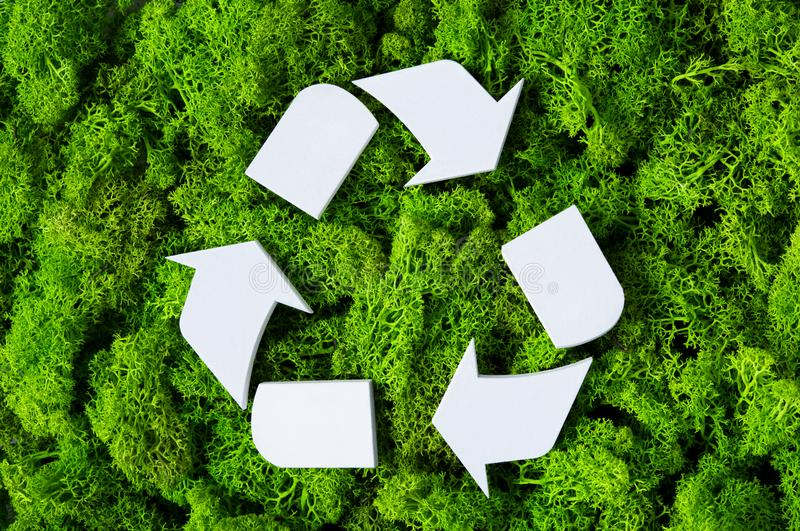 Recycle eco symbol. Top view of white recycle eco symbol on green moss with copy space. High angle view of recycled sign and eco concept on green background royalty free stock photography