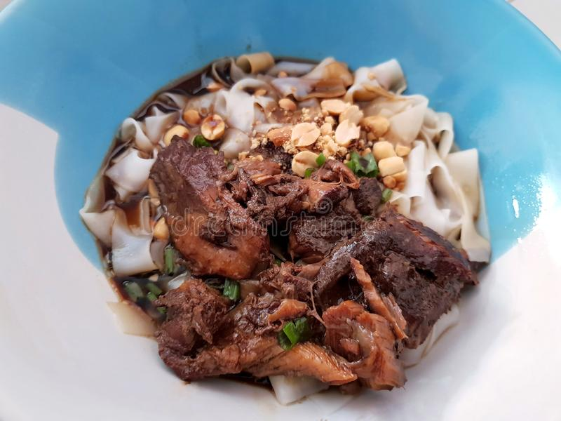 Top view of white rice noodle without soup topped with sliced pork and peanuts in bowl stock photos