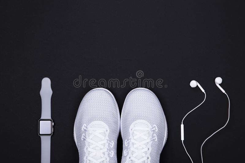White sport shoes sneakers with smart watch activity tracker and earphones headphones on black color background. royalty free stock photos