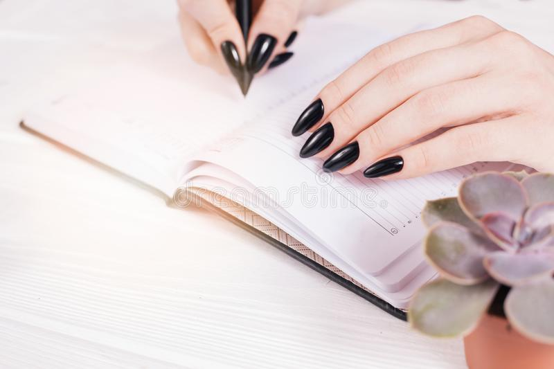 Top view on white wooden table with empty diary and girl`s hands with pen, free space. Girl`s hands writing in diary. Salon royalty free stock images