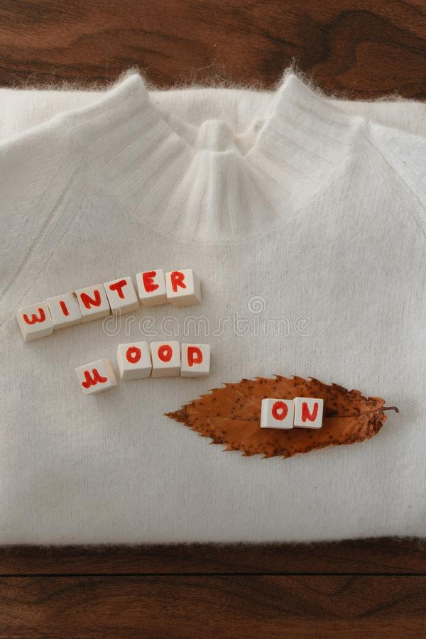 Top view of white woolen sweater with `Winter mood ON` text stock photo
